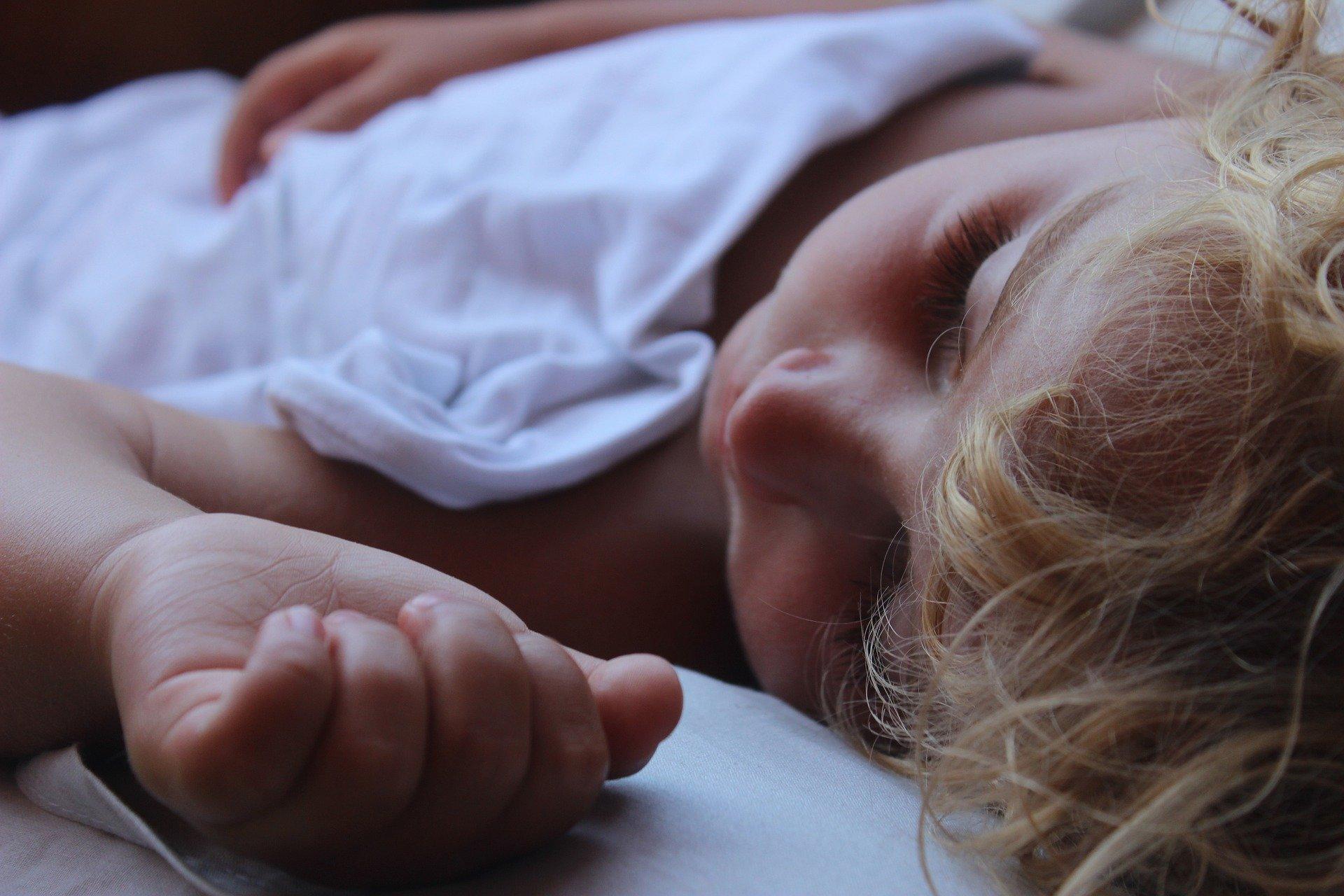 Dzecko śpiące w łóżeczku dziecięcym.