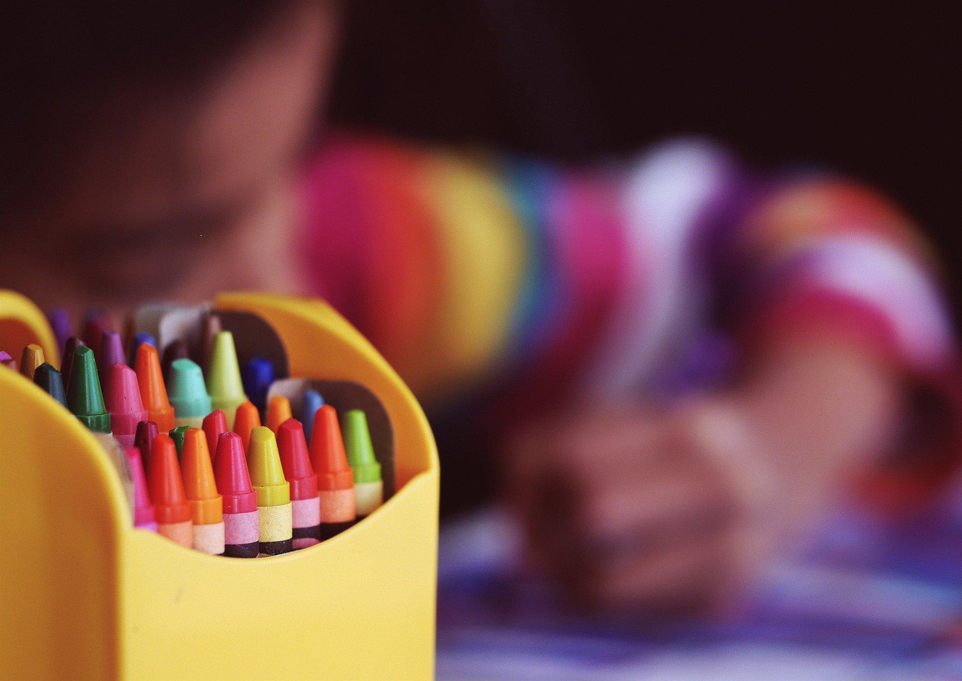 Dziecko rysujące kredkami w pokoiku dziecięcym.